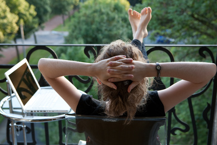 junge blonde Frau entspannt, Füße hoch, vor Laptop auf Balkon