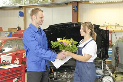 Der Meister gratuliert seiner Auszubildenden zur bestandenen Prüfung in der Autowerkstatt.